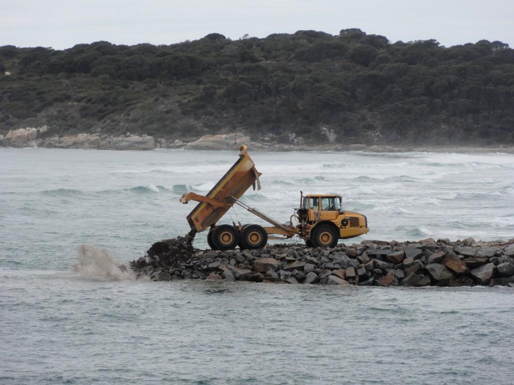 Dump truck off loads stone